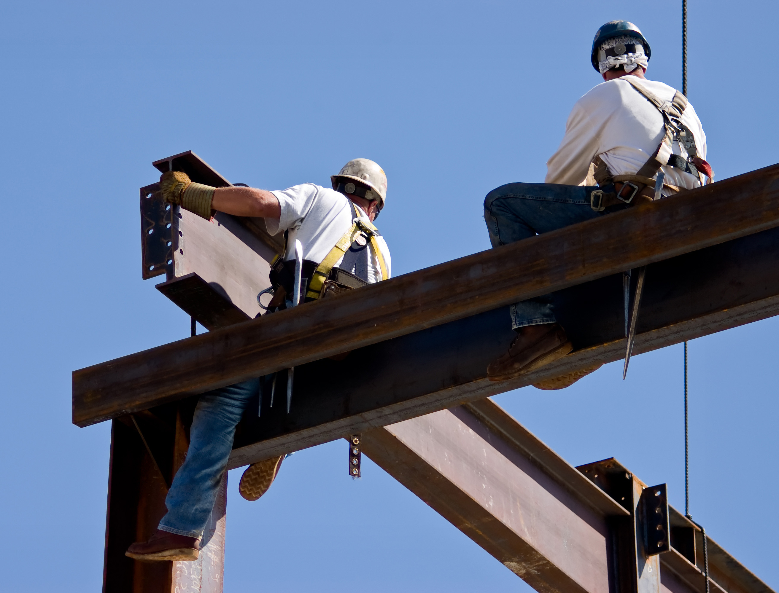 Two ironworkers atop the skeleton of a modern building. One man is positioning a very large beam while the other man watches.